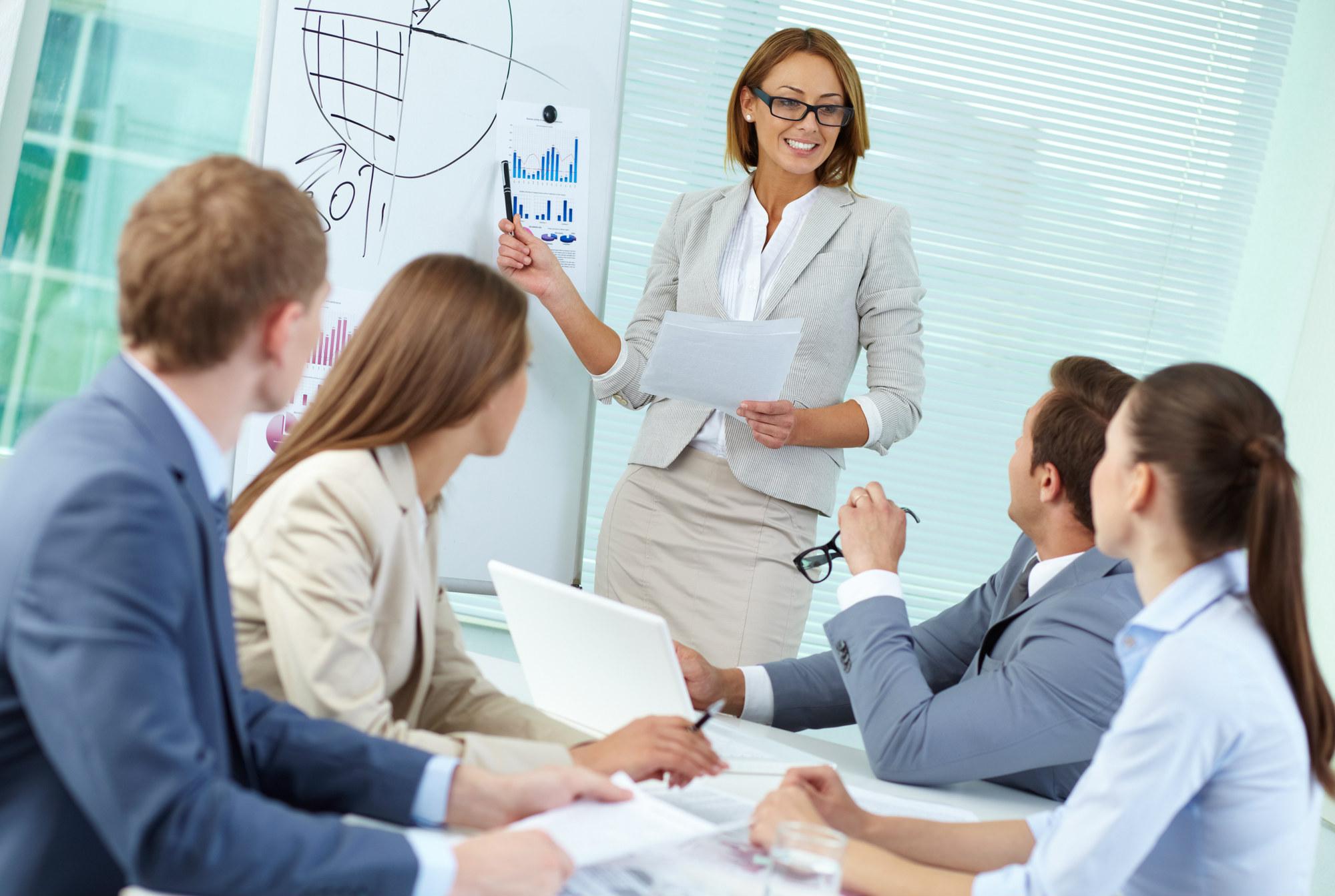 На фото – женщина ведет обучение группы